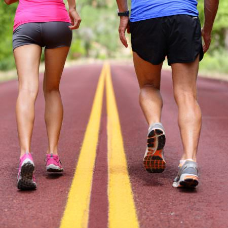 Running people. Runners jogging close up of sport fitness running shoes and legs and shorts. Athletes, woman and man in outdoor workout training for health and fitness.